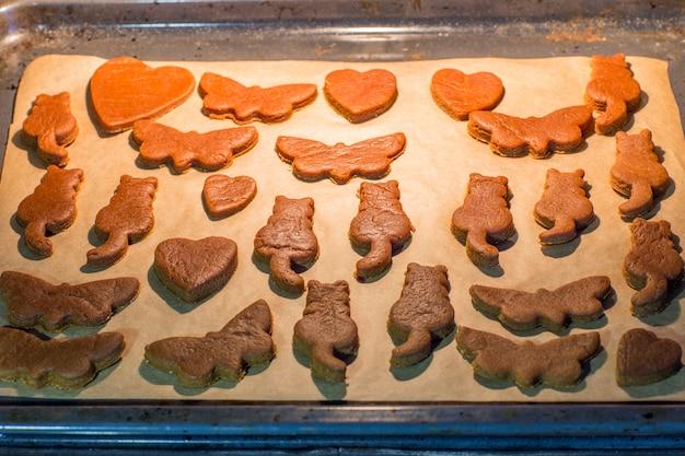 Biscoitos de gengibre em forma de borboletas, corações, gatos, preparando-se em uma assadeira no forno para o feriado