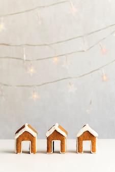 Biscoitos de gengibre em forma de casa. três casas de gengibre em fundo de guirlandas. quadro vertical.