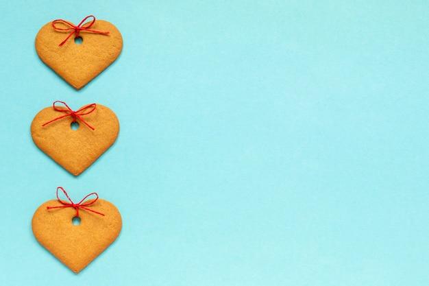 Biscoitos de gengibre em forma de coração decorado com um laço em fundo azul