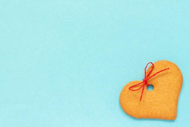 Biscoitos de gengibre em forma de coração decorado com um laço em um fundo azul