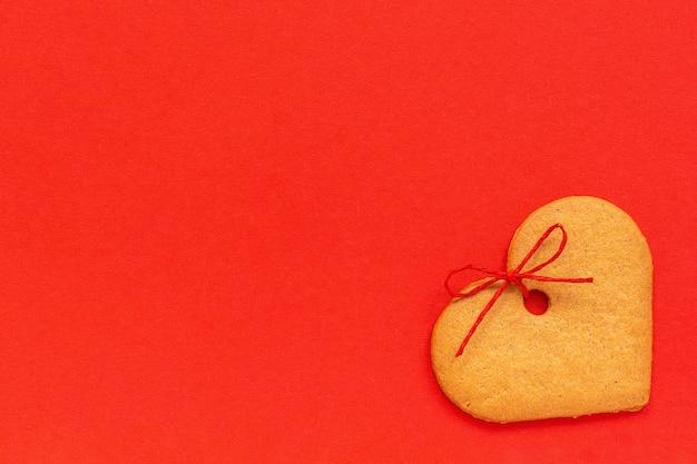 Biscoitos de gengibre em forma de coração decorado com um laço em um fundo vermelho