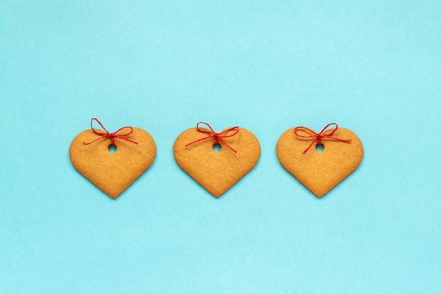 Biscoitos de gengibre em forma de coração decorado com um laço no fundo azul cartão de dia dos namorados