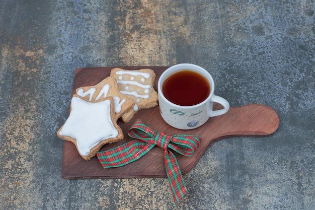 Biscoitos de gengibre em forma de estrela e uma xícara de chá na placa de madeira. foto de alta qualidade
