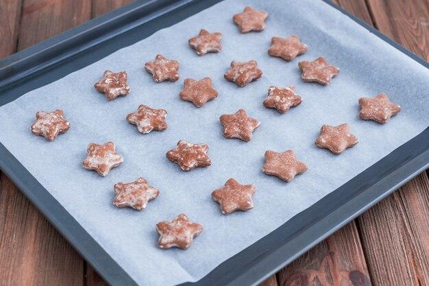 Biscoitos de gengibre em forma de estrela na bandeja de cozimento.