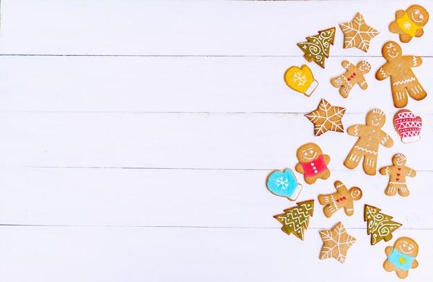 Biscoitos de gengibre em forma de homens, estrelas e árvores de saco e superfície de madeira branca. conceito de natal