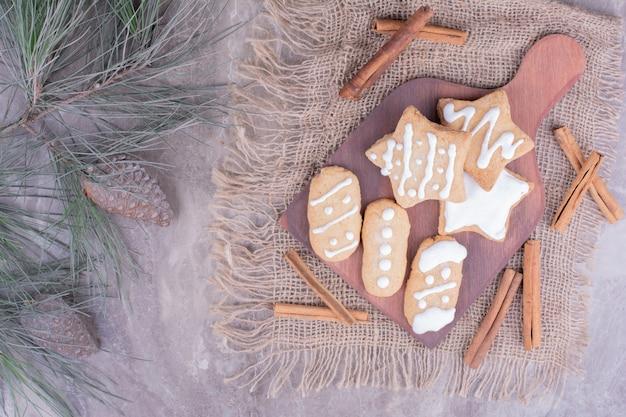 Biscoitos de gengibre em formas de estrela e oval com paus de canela na travessa de madeira.