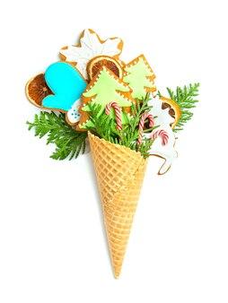 Biscoitos de gengibre em um cone de waffle em uma parede branca e isolada. galhos de thuja, pirulitos e flocos de neve.