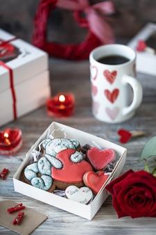 Biscoitos de gengibre em uma caixa de presente com velas, rosas e xícara de café