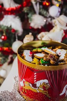 Biscoitos de gengibre em uma grande caixa vermelha na árvore de natal.