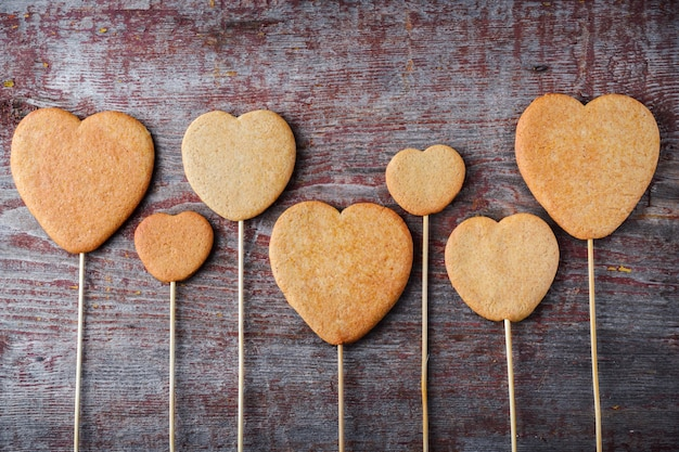 Biscoitos de gengibre em uma vara em forma de corações alinhados em uma mesa de madeira.