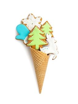 Biscoitos de gengibre encaracolados em um cone de waffle em uma parede branca e isolada. estatuetas de árvores de natal, flocos de neve, veados.