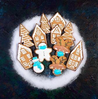 Biscoitos de gengibre engraçados em máscaras protetoras entre casas de pão de gengibre e abetos