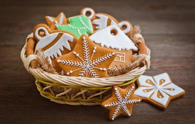 Biscoitos de gengibre festivos de natal em forma de estrela repousam sobre uma superfície de madeira marrom-escura