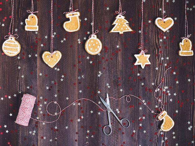 Biscoitos de gengibre na corda para a decoração da árvore de natal com tesoura e fio de ano novo na mesa de madeira
