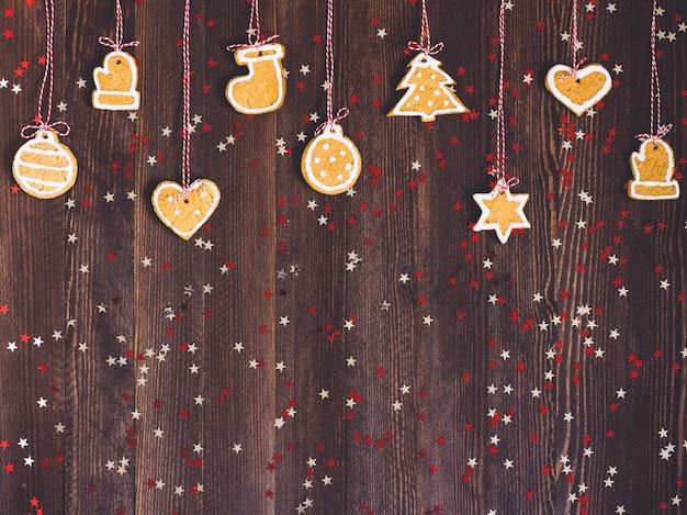 Biscoitos de gengibre na corda para a decoração da árvore de natal reveillon na mesa de madeira