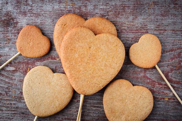 Biscoitos de gengibre no palito em forma de corações são empilhados em uma pilha sobre uma mesa de madeira