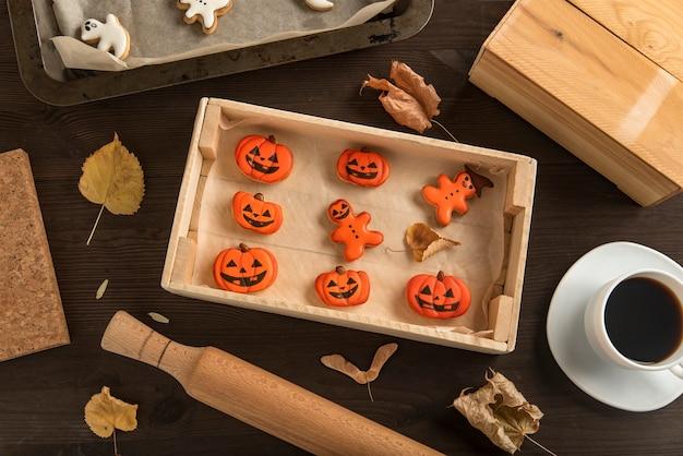 Biscoitos de gengibre para o halloween mentem em uma forma de madeira em cima da mesa. em forma de abóbora. muito gostoso para comer com uma xícara de café