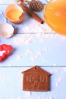 Biscoitos de gengibre pequena casa bolos caseiros de natal em um fundo rústico de madeira claro foco suave estilo rústico
