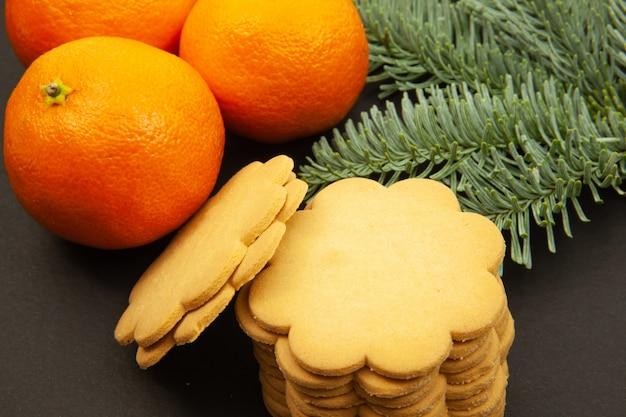 Biscoitos de gengibre, ramos de pinheiro e tangerinas, sobre um fundo escuro, close-up