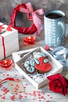 Biscoitos de gengibre, xícara de café, flor rosa e coroa em forma de coração