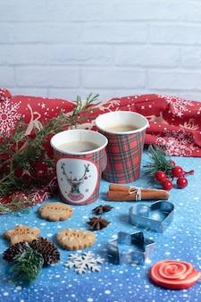 Biscoitos de gengibre, xícaras de café aromático e pirulito no azul