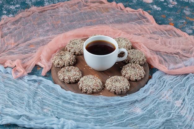 Biscoitos de gergelim de gengibre em uma bandeja de madeira.