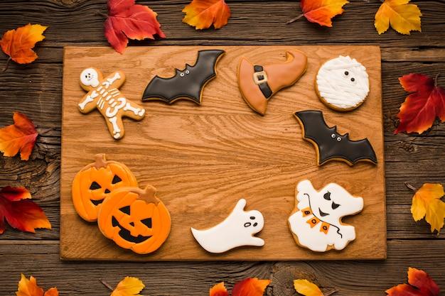 Biscoitos de halloween de vista superior em uma placa de madeira
