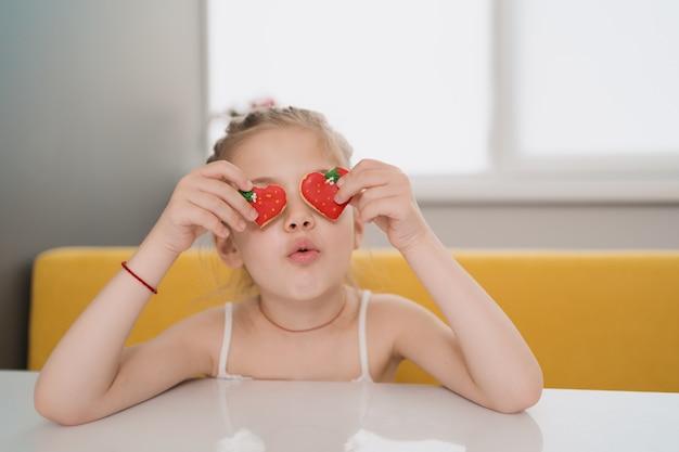 Biscoitos de holdig adorável criança sobre os olhos