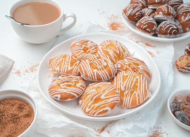 Biscoitos de limão e bolos pequenos éclair em um fundo branco. vista superior, horizontal.
