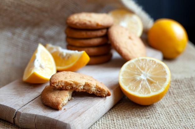 Biscoitos de limão e rodelas de limão em uma placa de madeira