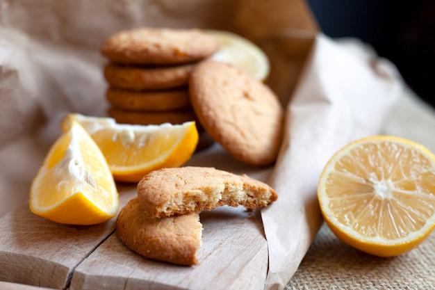 Biscoitos de limão feitos em casa, assar cítricos deliciosamente fica sobre uma mesa em uma embalagem de papel, uma receita para assar frutas