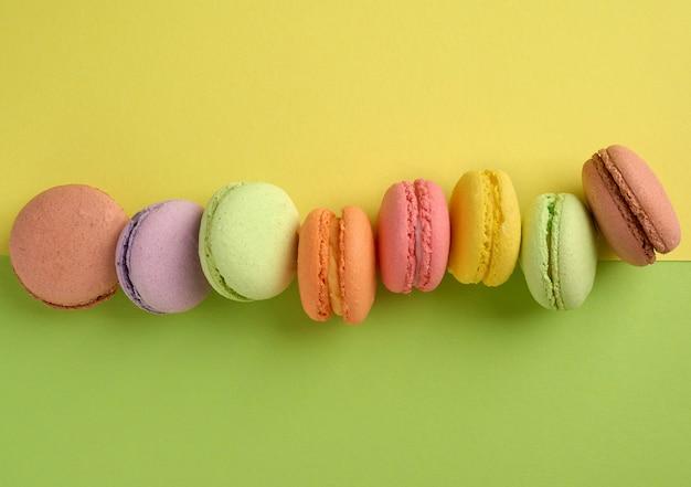 Biscoitos de macaroon multicoloridos assados em uma fileira em um verde-amarelo