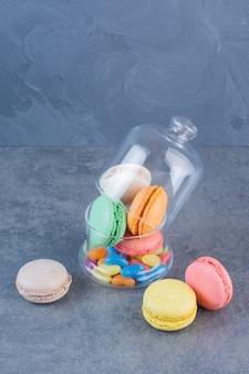 Biscoitos de macarrão de cores diferentes em uma jarra de vidro colocada sobre a mesa cinza