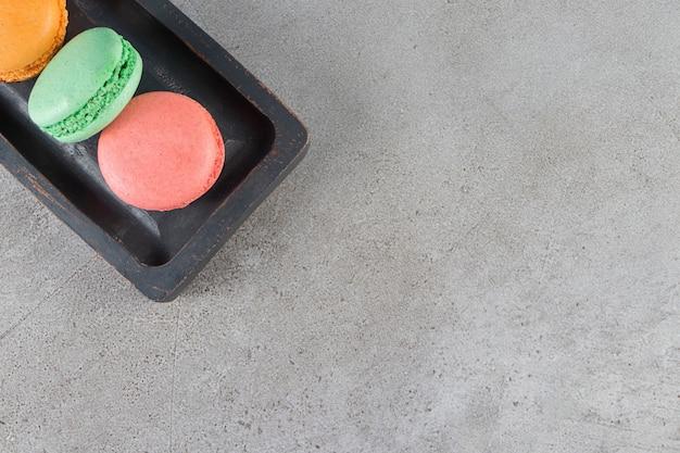 Biscoitos de macarrão de cores diferentes em uma placa de madeira escura