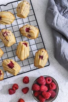Biscoitos de madeleine artesanais de framboesa no rack de refrigeração na mesa cinza