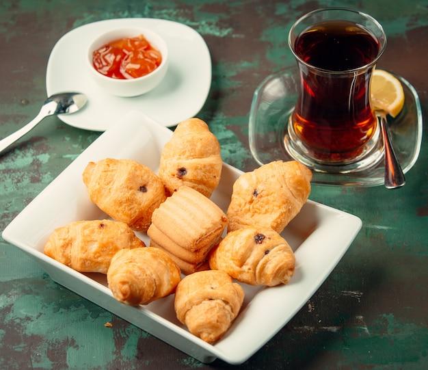 Biscoitos de manteiga com passas, servidos com chá e geléia