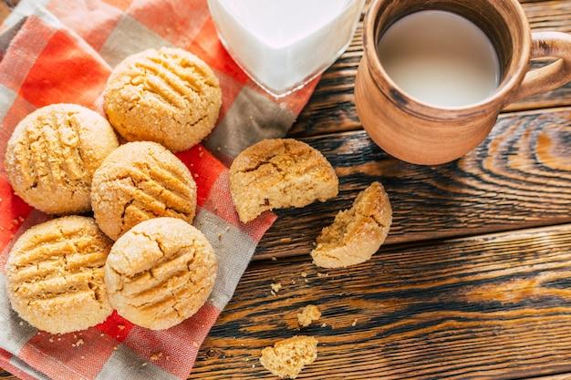 Biscoitos de manteiga de amendoim e caneca de argila com leite no fundo de madeira