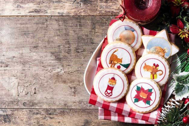 Biscoitos de manteiga de natal decorados com gráficos de natal na mesa de madeira, copyspace