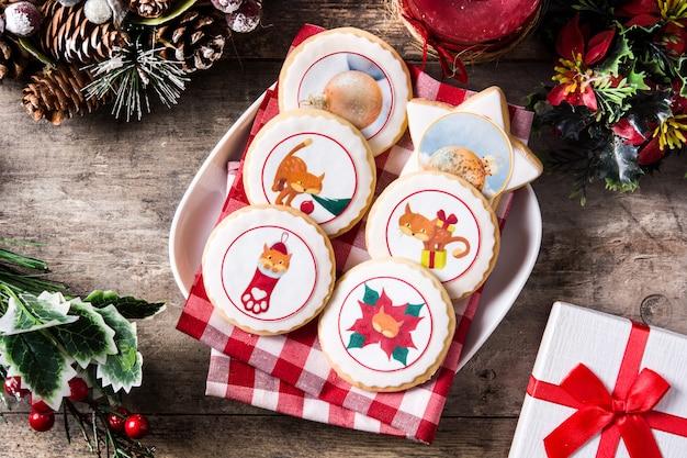 Biscoitos de manteiga de natal decorados com gráficos de natal, na mesa de madeira