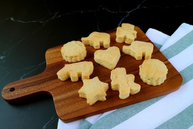 Biscoitos de manteiga deliciosos caseiros deliciosos na tábua de pão de madeira no fundo preto