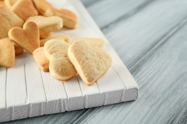 Biscoitos de manteiga em forma de coração na mesa de madeira