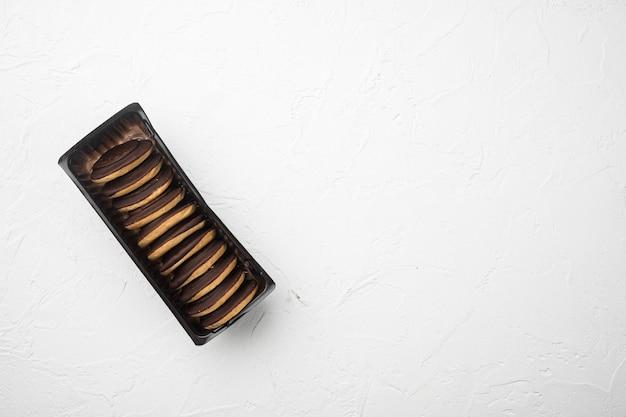 Biscoitos de marshmallow com cobertura de chocolate, em bandeja de plástico, em bandeja de plástico, fundo de mesa de pedra branca, vista de cima plana, com espaço de cópia para o texto