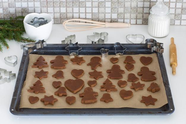 Biscoitos de massa de gengibre são colocados em uma assadeira na mesa da cozinha