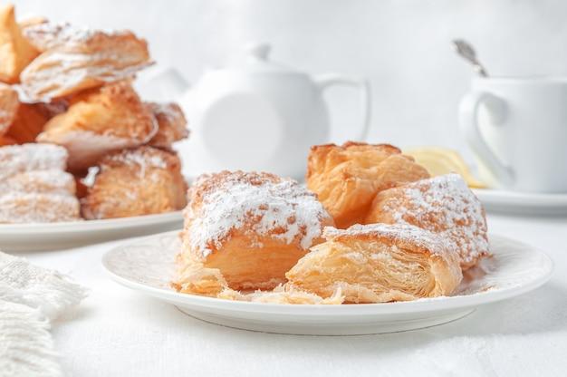 Biscoitos de massa folhada quadrados polvilhados com açúcar de confeiteiro caseiro em um prato branco no fundo está uma caneca de porcelana branca e um bule. fundo branco de tecido close
