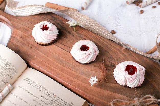 Biscoitos de merengue com geléia de morango em uma placa de madeira
