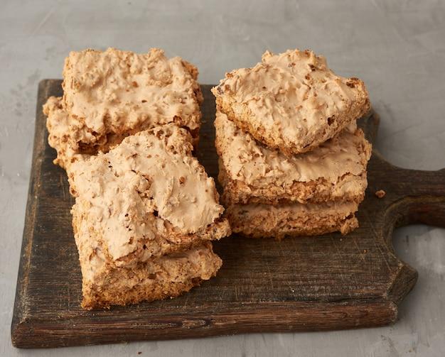 Biscoitos de merengue cozidos em cracóvia em uma placa de madeira, deliciosa sobremesa de claras de ovo batidas