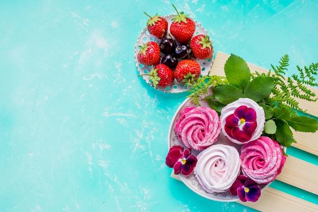 Biscoitos de merengue rosa com frutas para a sobremesa