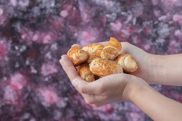 Biscoitos de mutaki fritos na mão do cozinheiro.