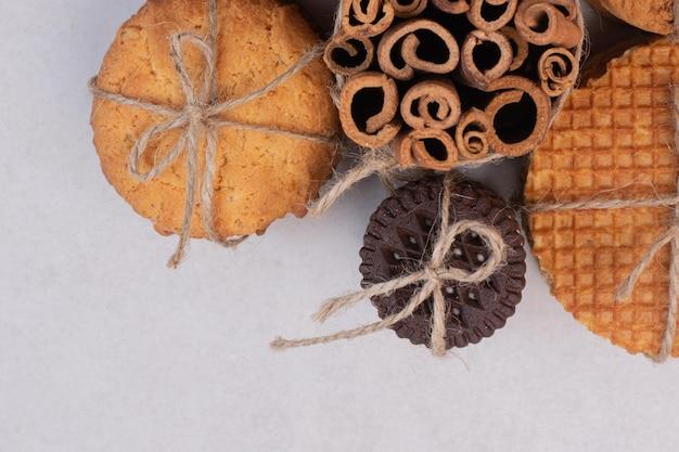 Biscoitos de natal com canela em corda na mesa branca.