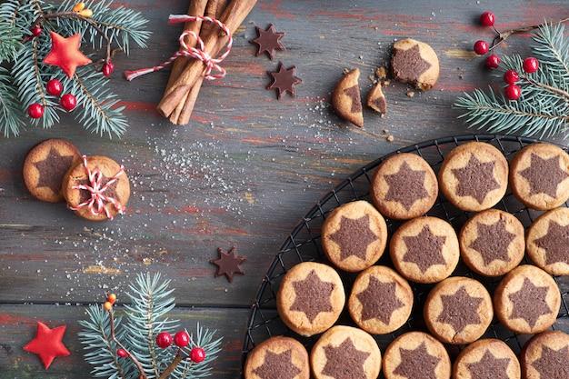 Biscoitos de natal com chocolate estrela no rack de arrefecimento com especiarias e decorado galhos de pinheiro